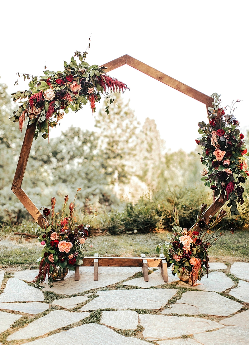 Wooden geometric wedding arch with floral swag for bohemian ceremony