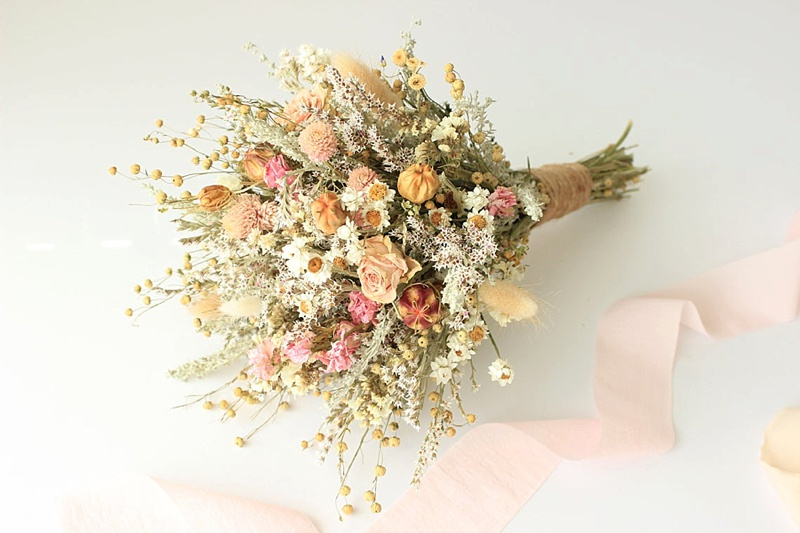 Dried pink and peach colored floral wedding bouquet for cottagecore wedding day