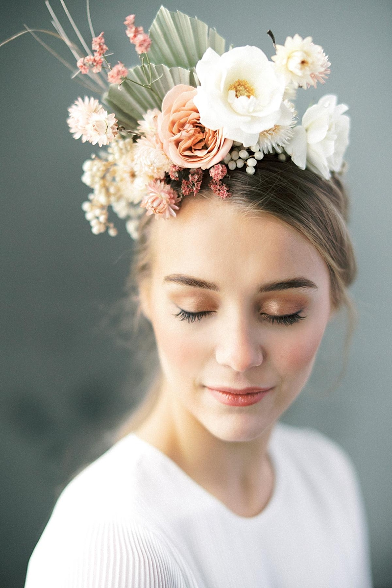 Beautifully chic romantic bridal floral headpiece with small dried palm leaves and flowers for a stylish wedding look