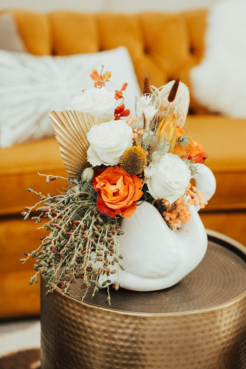 Colorfully orange and white wedding centerpiece with dried palm leaves in a fun modern swan shaped vase