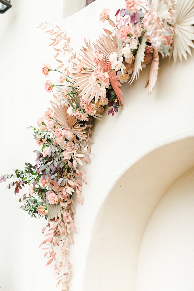 Beautiful pastel pink painted dried florals and palm leaves for a lovely wedding ceremony arch on a building wall