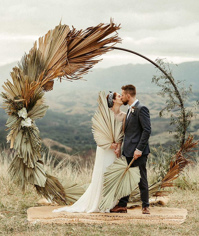 Modern metal wedding ceremony arch with giant dried palm leaves for a unique boho destination style