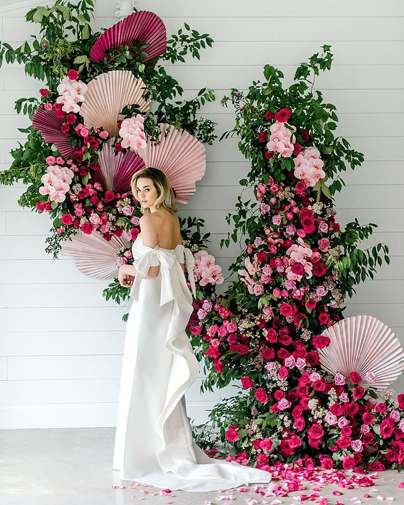 Luxurious wedding floral backdrop with greenery and orchids and painted pink dried palm leaves for a modern tropical wedding day