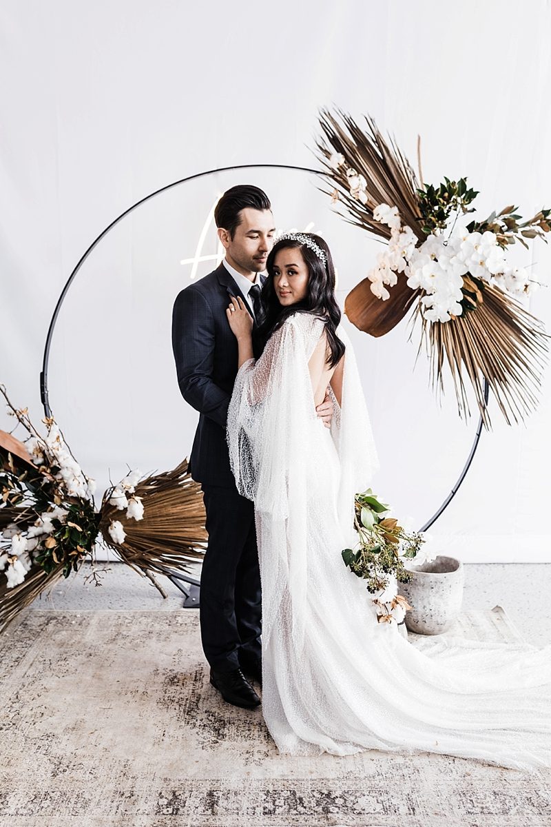 Round metal circle wedding ceremony arch with orchids and dried sun palm leaves for chic modern boho wedding