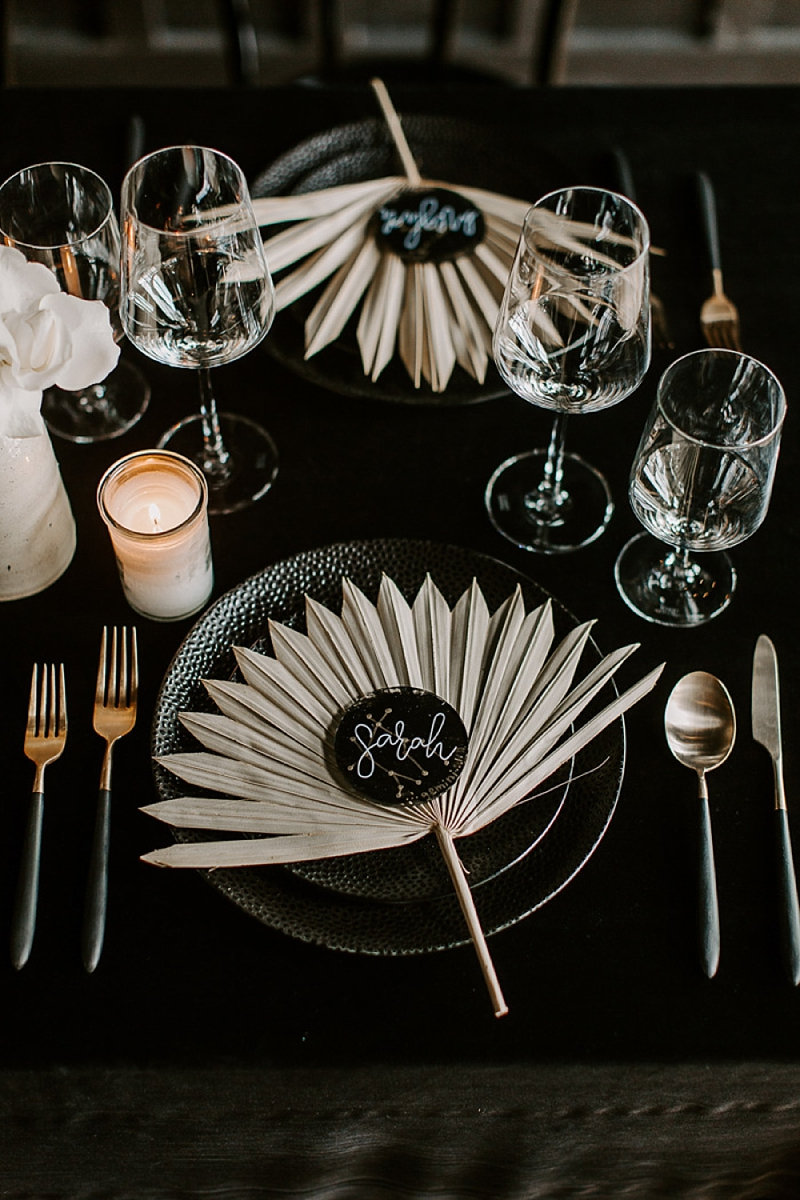 Celestially inspired wedding place settings with dried sun spear palm leaves as unique placemats and starry constellations for place cards