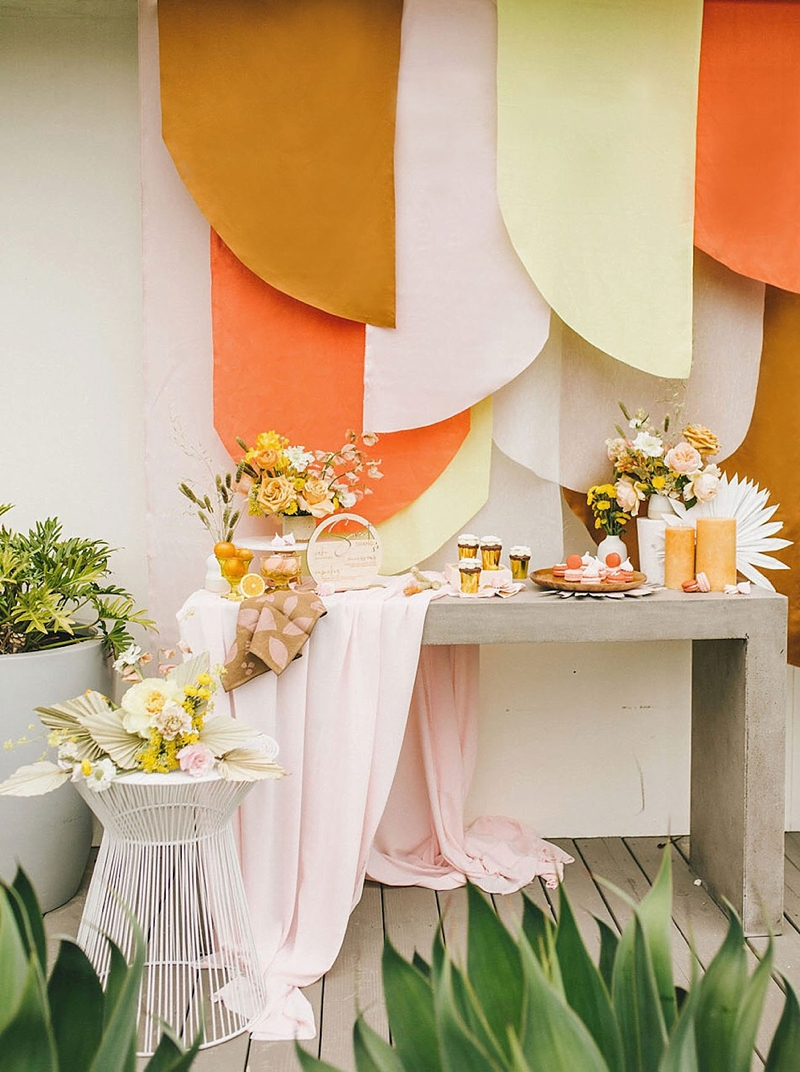 Colorful retro wedding ideas with white painted dried sun spear palm leaves and layered fabric backdrop for concrete cake dessert table