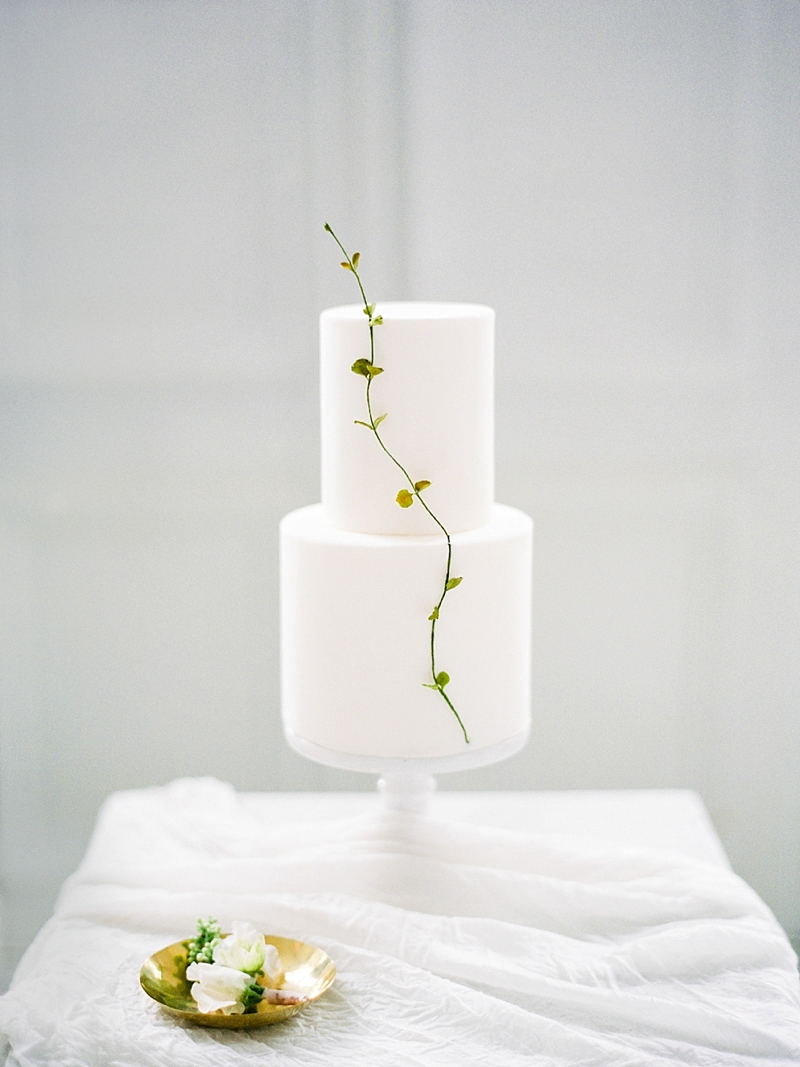 Modern minimalist white tiered wedding cake with single stem for a simple chic look