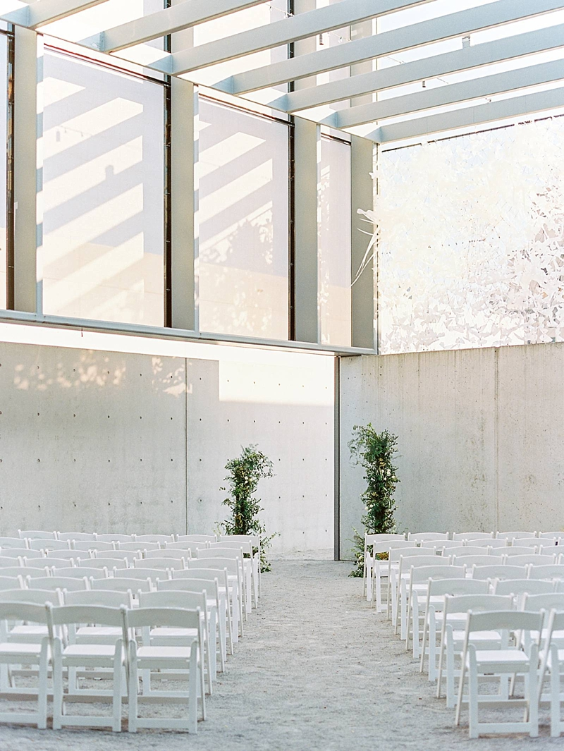 Two tall open greenery altar arrangements for minimalist wedding ceremony in an industrial venue space