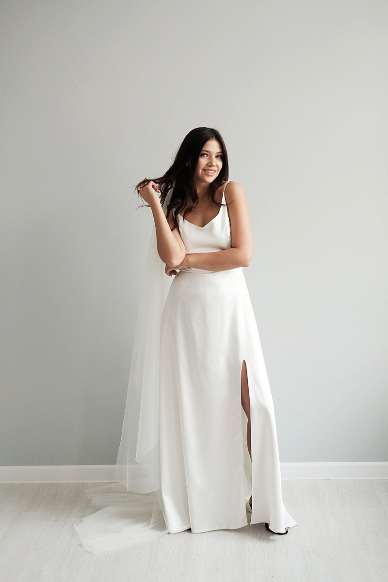 White minimalist wedding dress with spaghetti straps and open leg slit for a chic sexy bridal look