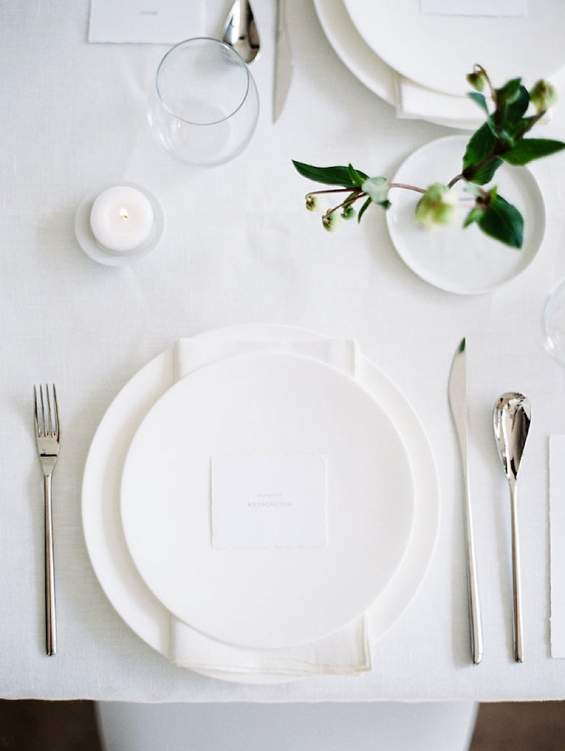 Simple and minimalist wedding place setting with small paper place card and white plates