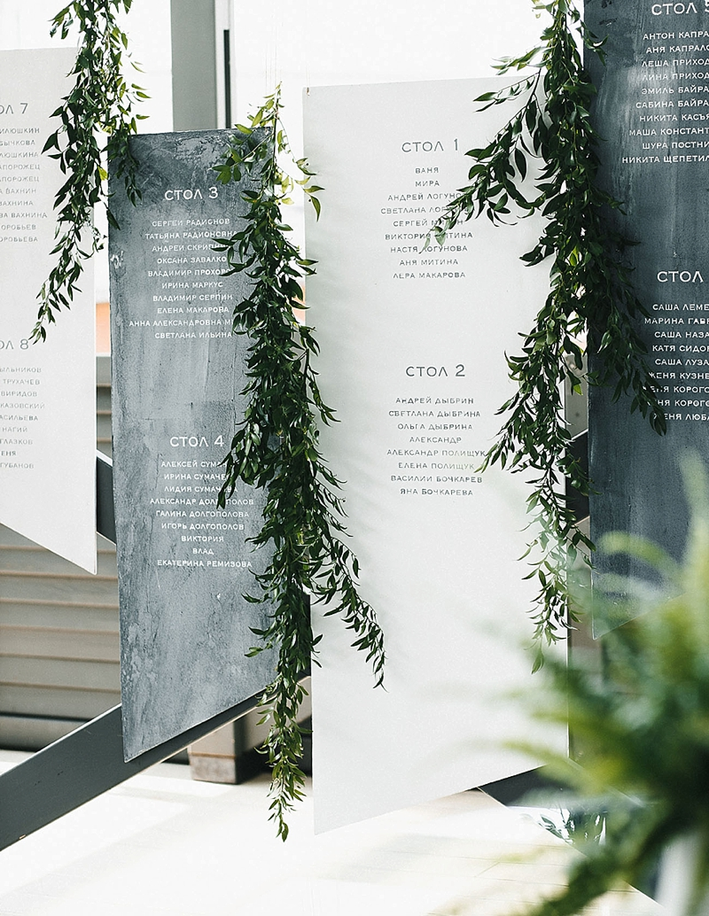 Hanging minimalist gray wedding seating chart with greenery
