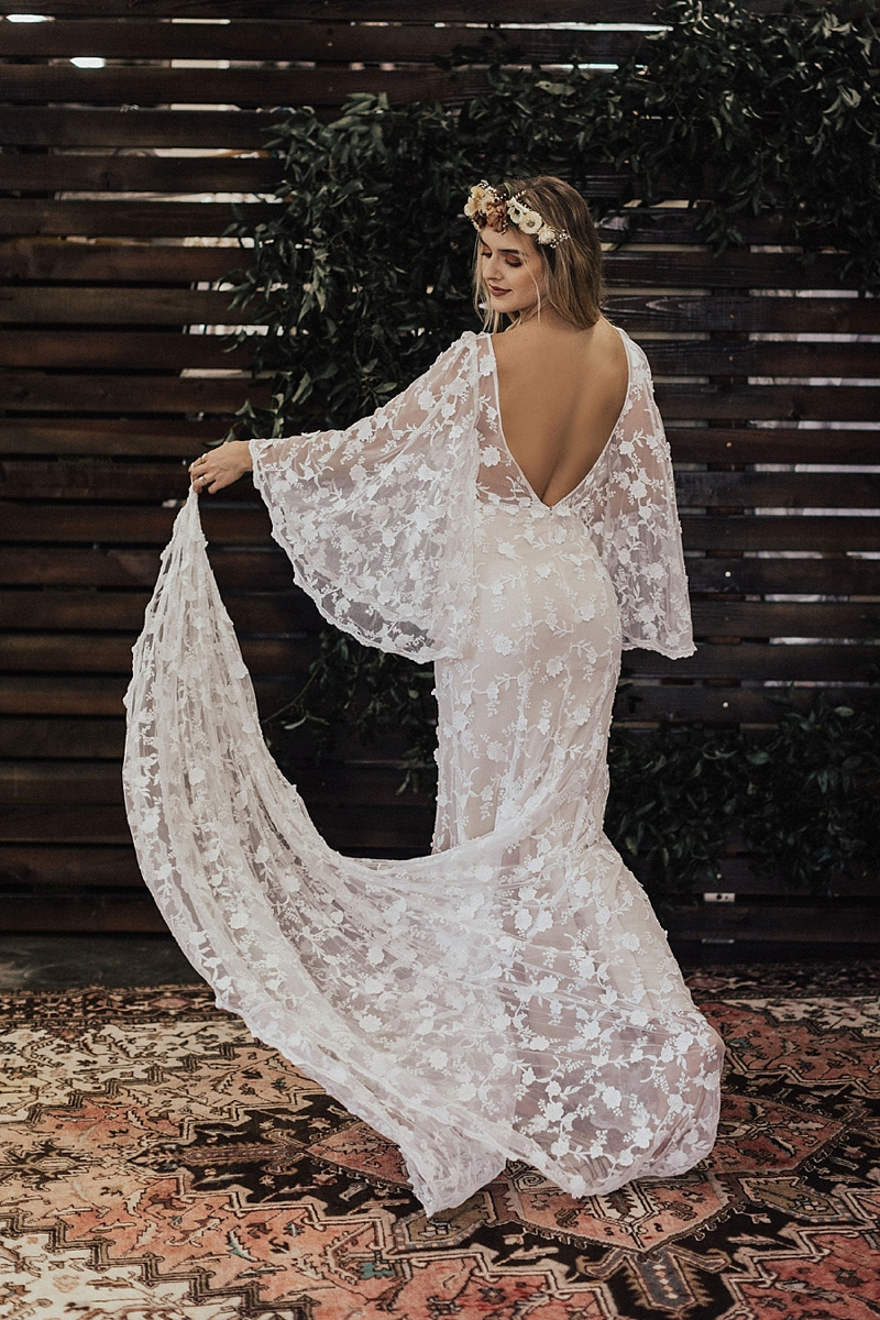 Backless bohemian lace bridal gown with large fluted sleeves and long train