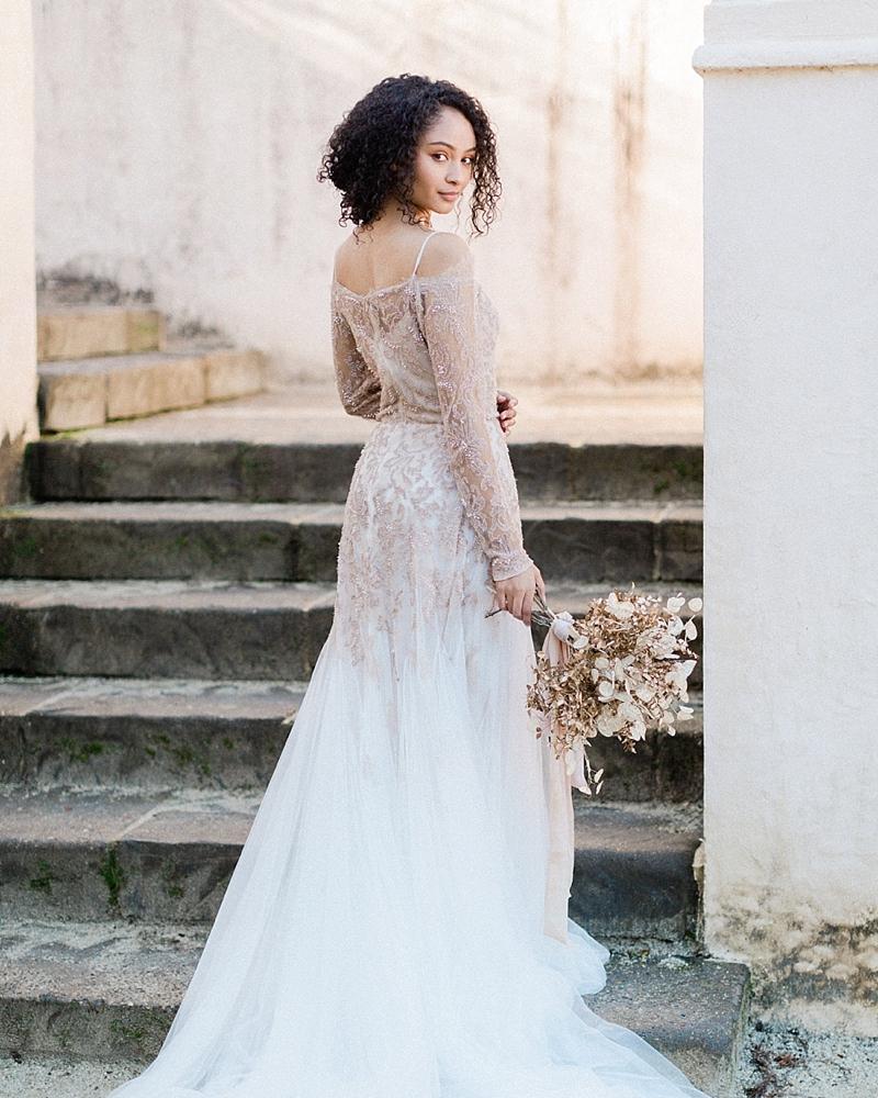 Elegant off the shoulder blush pink wedding dress with long sleeves and deep v neckline for vintage bride