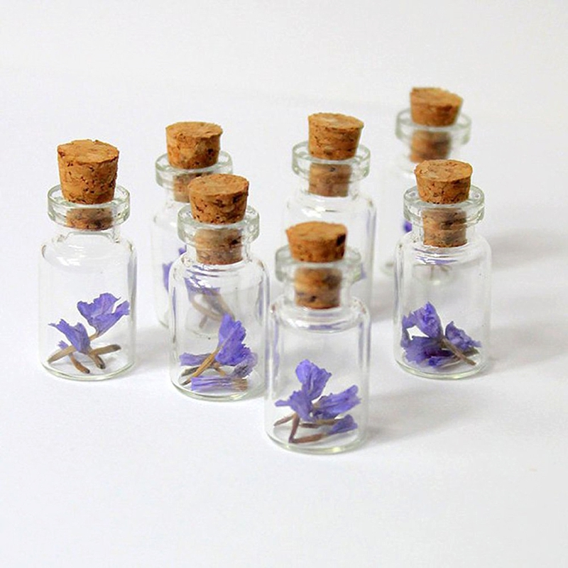 Purple flowers in tiny glass jars for sweet wedding favors