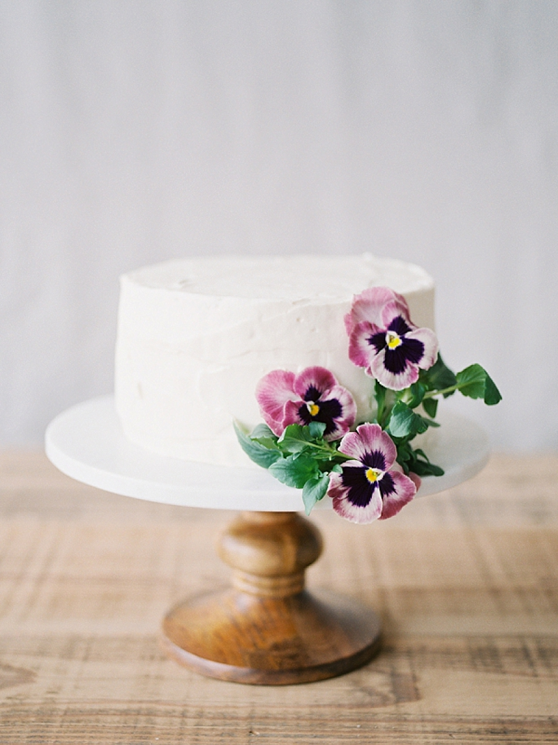 Single tier white wedding cake with purple flowers