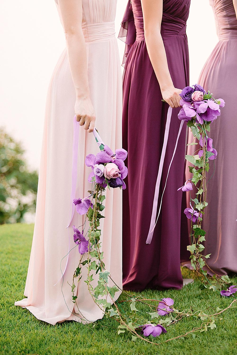 Draping purple bridesmaid bouquets with orchids and roses for tropical weddings