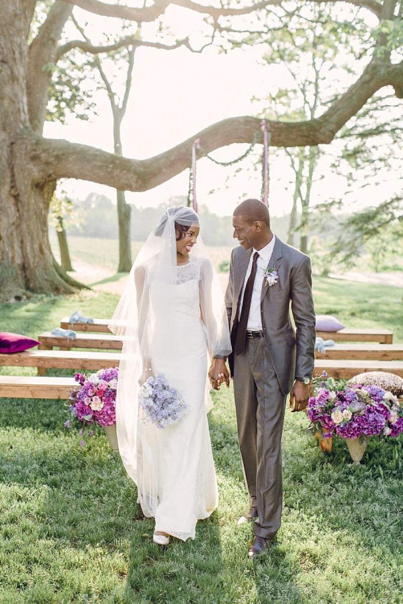 Romantic purple wedding ceremony decor with plum colored pillows and lilac flowers