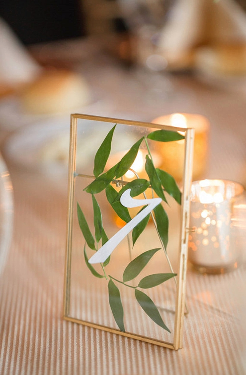 Pressed greenery in glass and gold frame for wedding table numbers