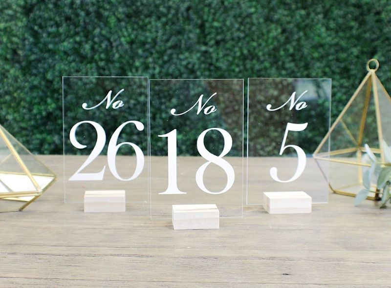 Simple clear transparent acrylic wedding table numbers on unpainted wood stands perfect for a modern wedding