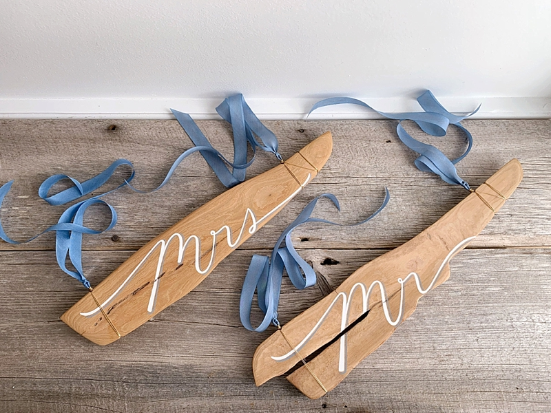 Calligraphy Mr and Mrs wedding chair signs written on beautiful driftwood with blue ribbons perfect for beach weddings