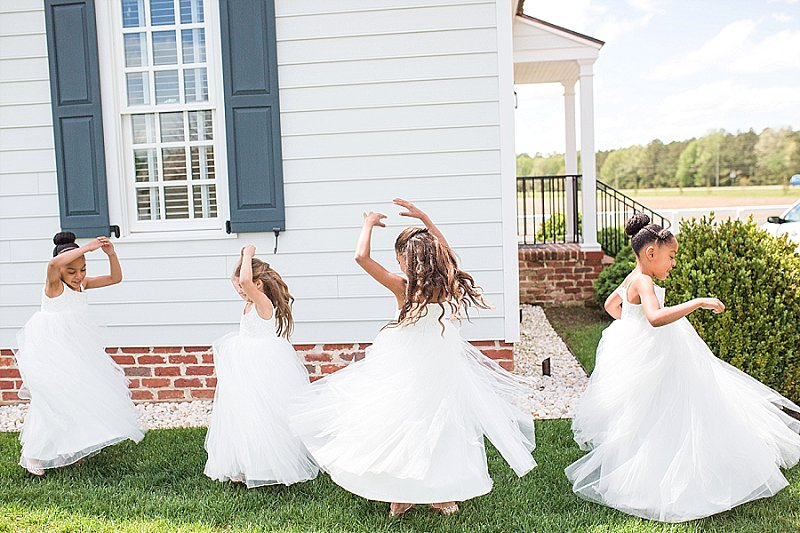 Adorable flower girls twirling around on the wedding day