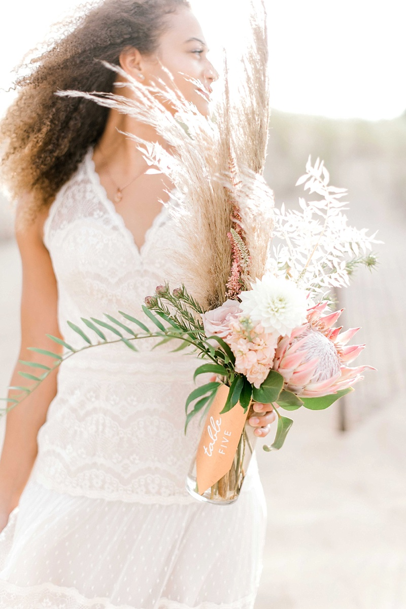 Wildly elegant boho wedding reception ideas with textured copper table numbers and protea and pampas grass