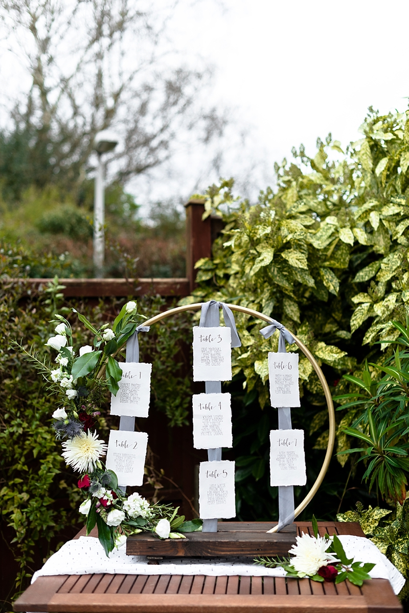 Elegant DIY wedding seating chart with silk ribbons and flowers made with a hula hoop and Rustoleum spray paint
