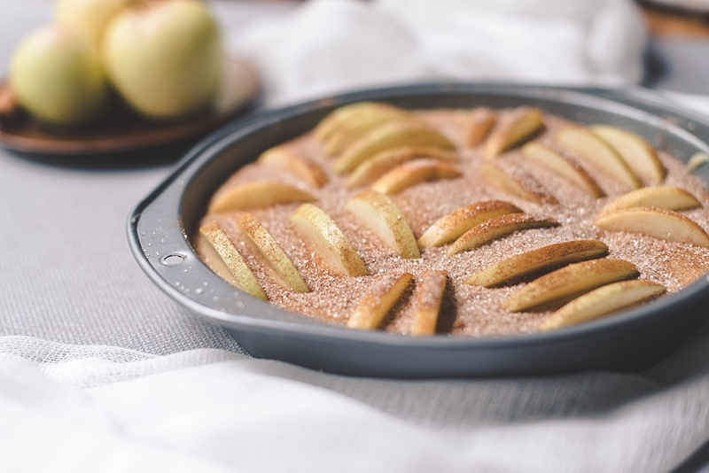 Cinnamon and sugar sprinkled on apple cider cake batter
