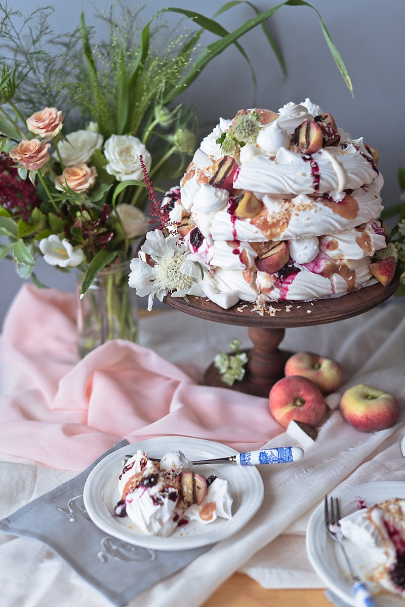 Summer inspired grilled peach and blueberry coconut pavlova meringue wedding cake on a dark brown cake stand and peach table runner