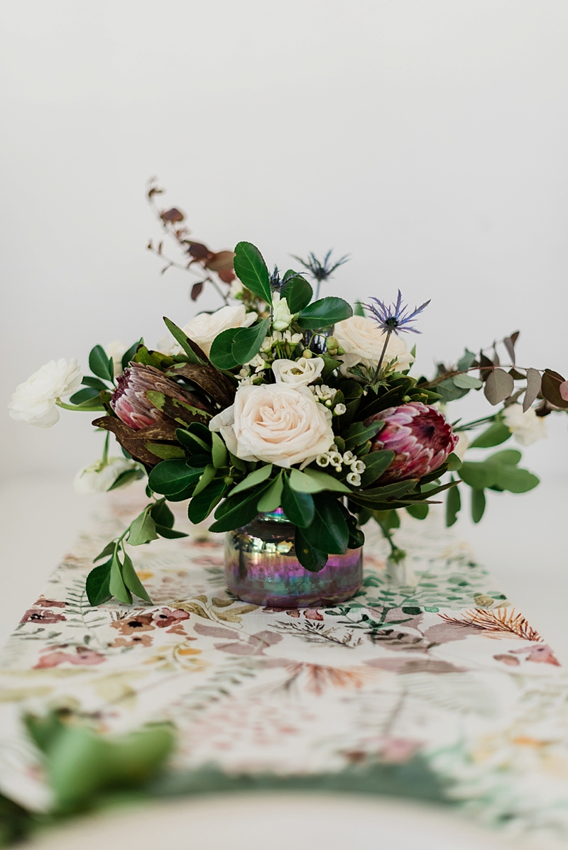 Gorgeous early spring inspired wedding or table centerpiece with protea and roses and wax flowers