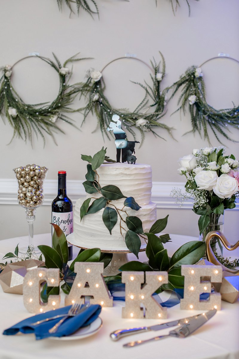 Simple two tiered white wedding cake with faux greenery and dog wedding cake topper
