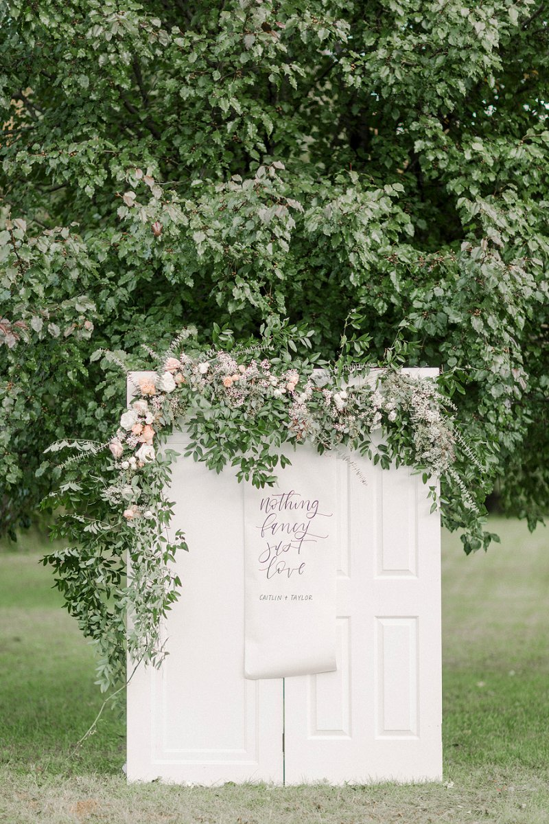 Gorgeous white door wedding ceremony altar decor with calligraphy banner and wild floral swag garland