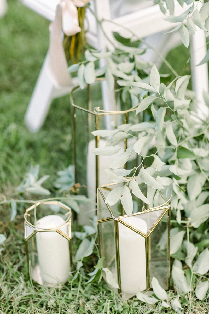 Gold geometric candle vases for modern rustic wedding ceremony aisle decor surrounded by greenery