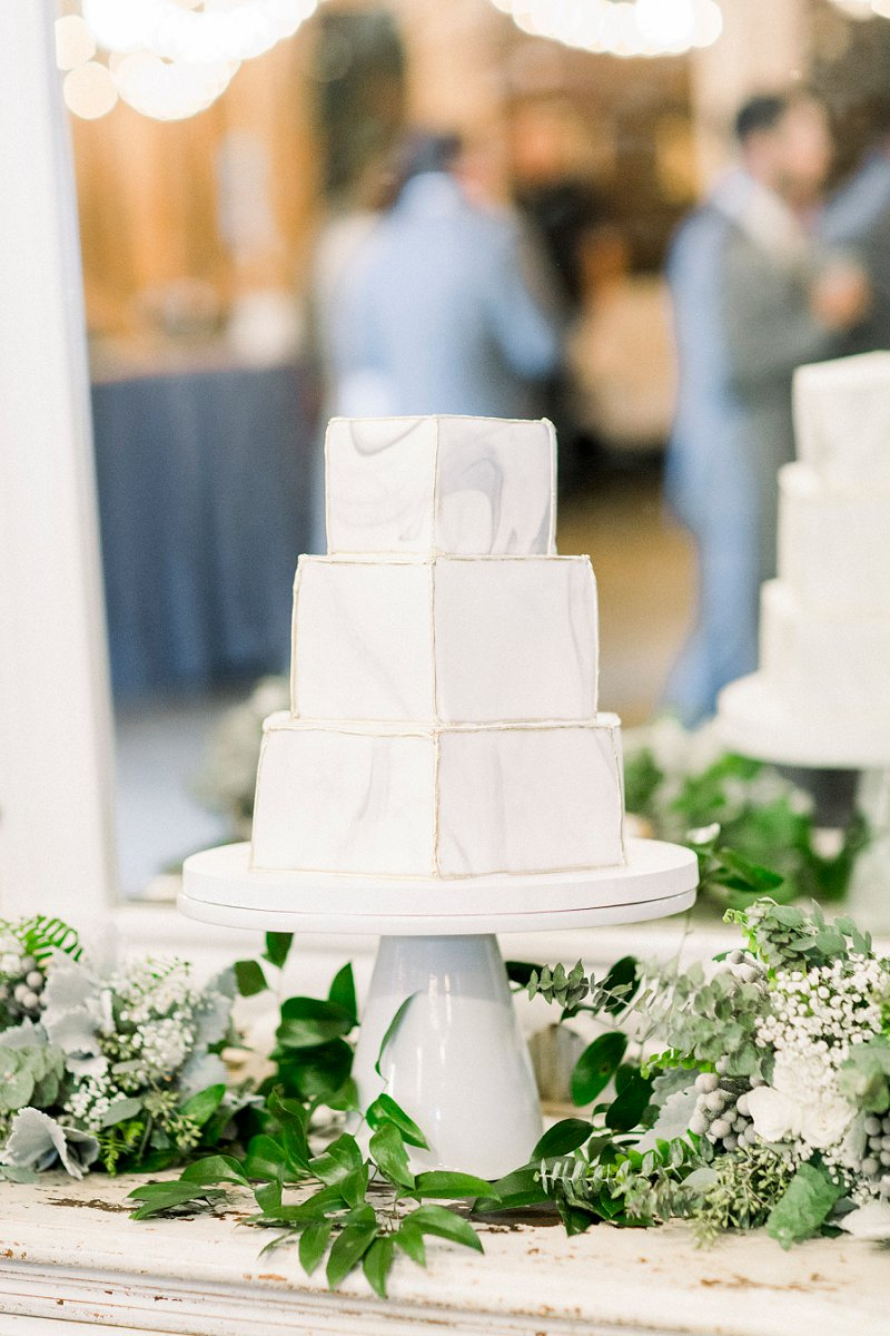 Gray and white marble painted three tiered wedding cake on a white cake stand for modern rustic wedding at Glasgow Farm in Fredericksburg Virginia