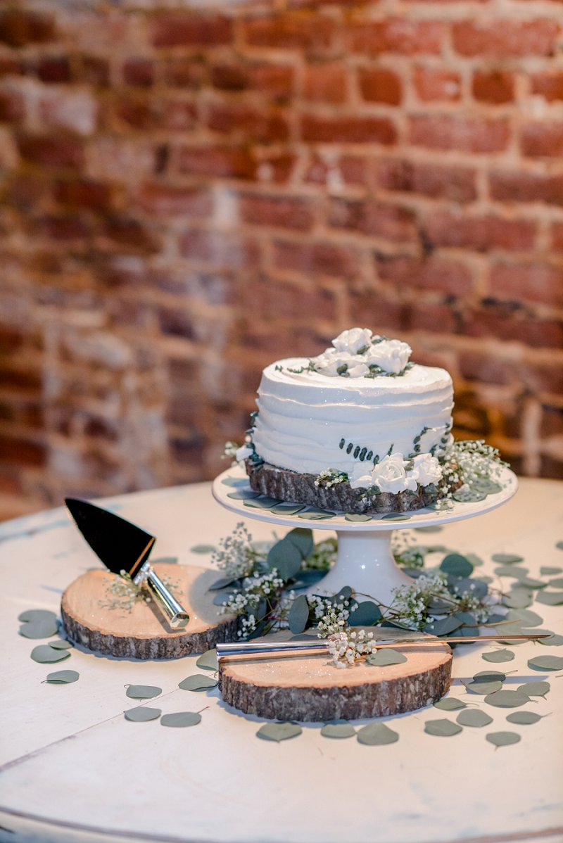 Rustic winter one tier layer wedding cake decorated with eucalyptus on a wood slab at Old Silk Mill in Virginia