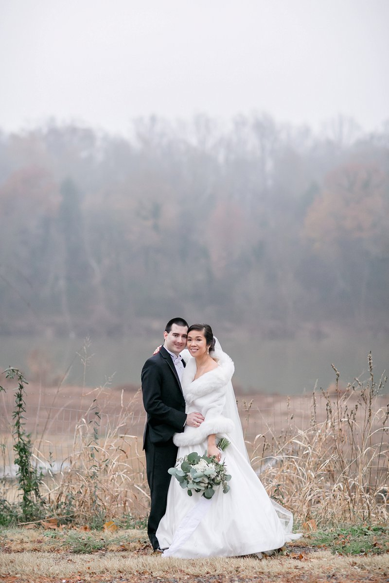 Classic bride and groom wearing black tuxedo and white faux fur winter cape for wedding at the Old Silk Mill in Fredericksburg Virginia