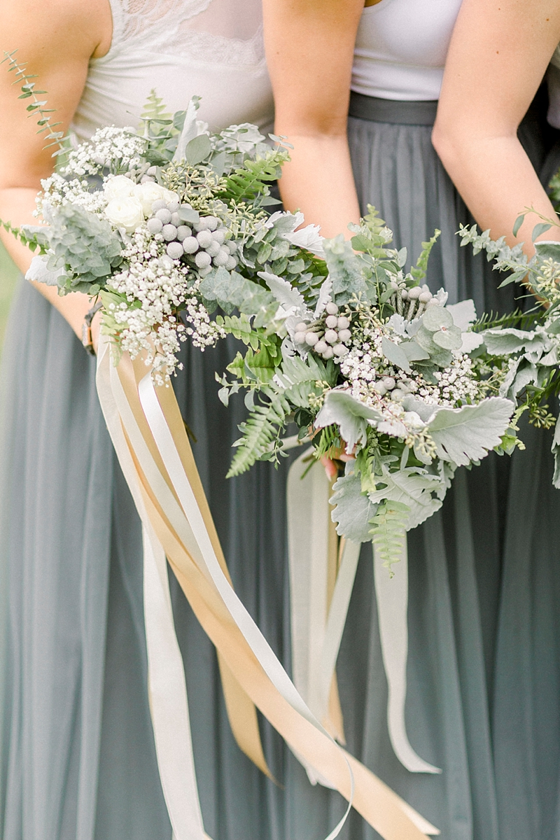 Silver and gray wedding flowers for timeless bridesmaid bouquets with long satin ribbons at a rustic wedding