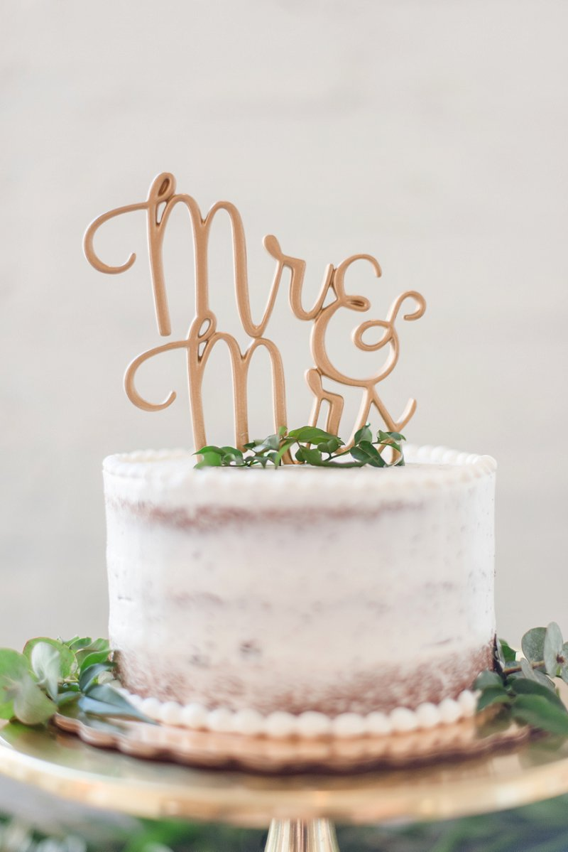 Simple semi naked one layer wedding cake with gold Mr and Mrs cake topper on a gold cake stand