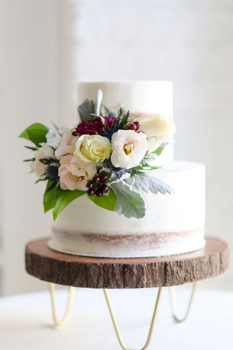 Sweet petite two tiered semi naked wedding cake on a modern wood slab cake stand for winter wedding