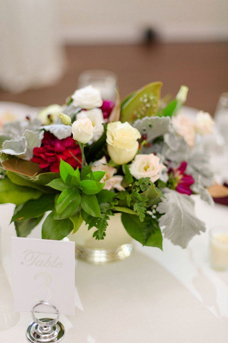 Simple low floral centerpiece with dusty miller and a silver table number for winter wedding idea