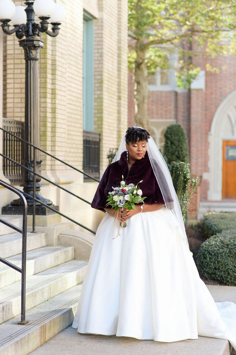 Gorgeous black bride with faux fur burgundy capelet and natural curls for her chic winter wedding in Hampton Roads Virginia