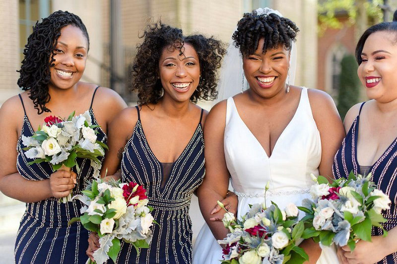 Beautiful bridesmaids in dark navy blue dresses with silver beaded details for winter wedding