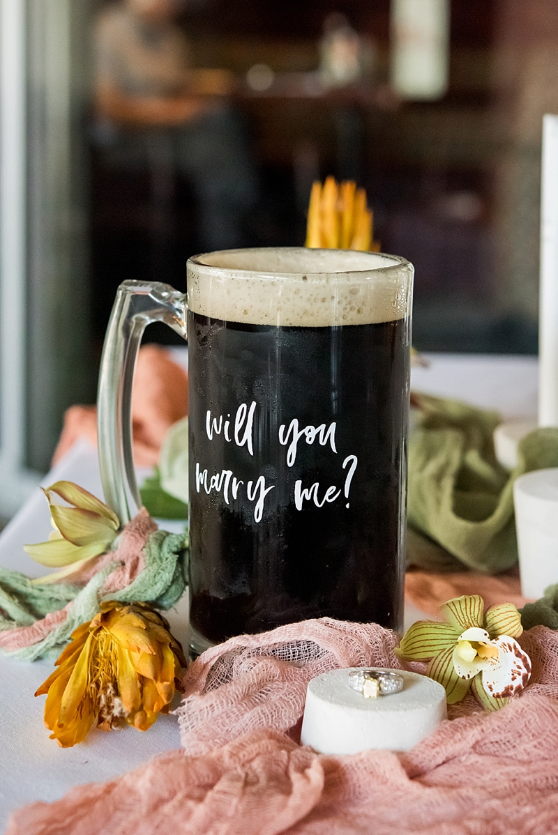 Unique way to propose with a mug of stout beer at a brewery restaurant