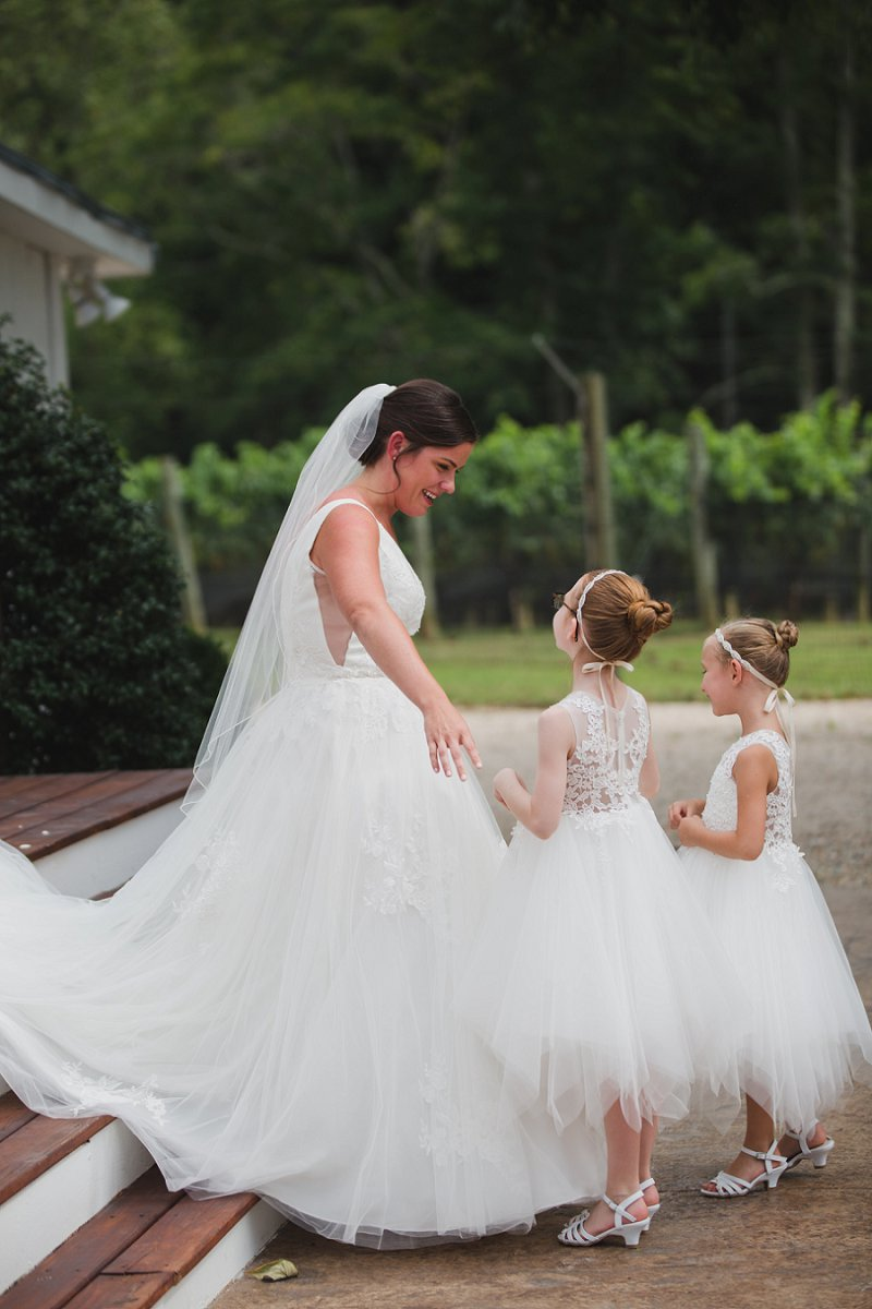 Beautiful candid photo moment between bride and her flower girls at New Kent Winery in Virginia