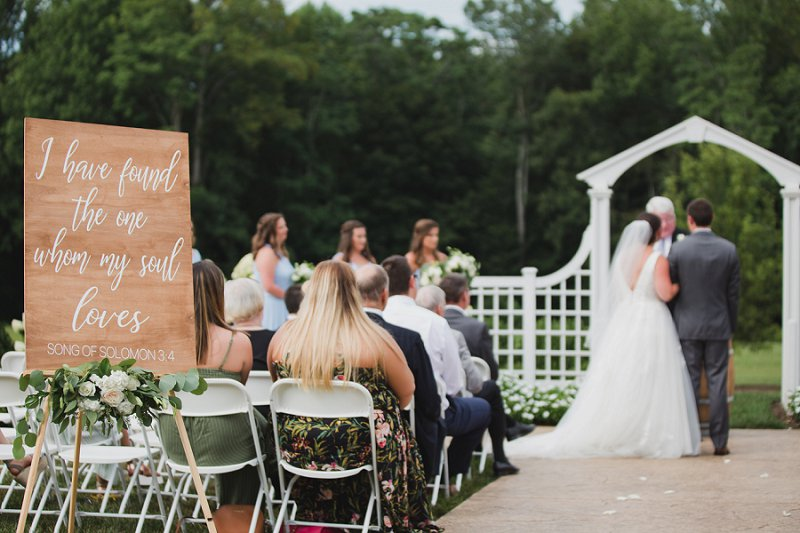 Outdoor rustic wedding ceremony with Song of Solomon Bible verse for a wedding welcome sign