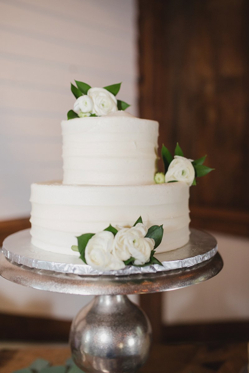 Simply textured two tier white wedding cake with ranunculus decoration on a silver cake stand