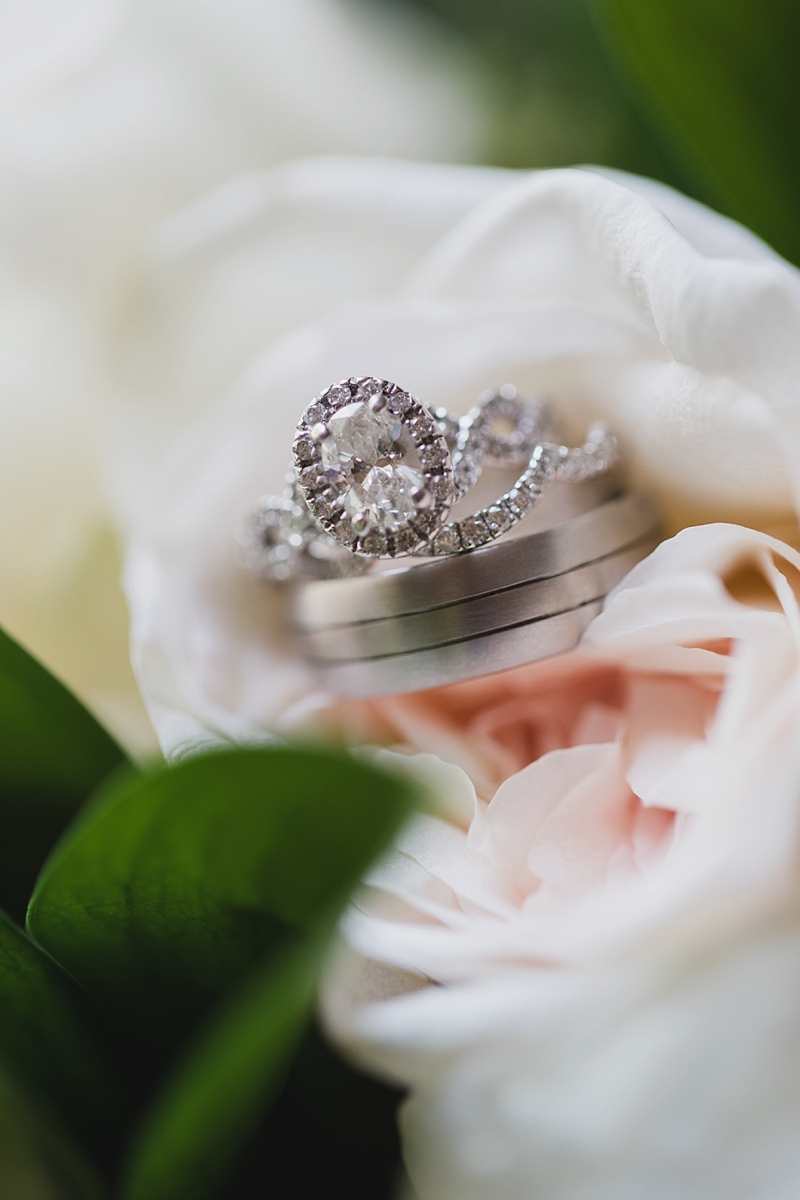 Sparkly oval wedding ring surrounded by small diamonds and silver wedding band with grooves