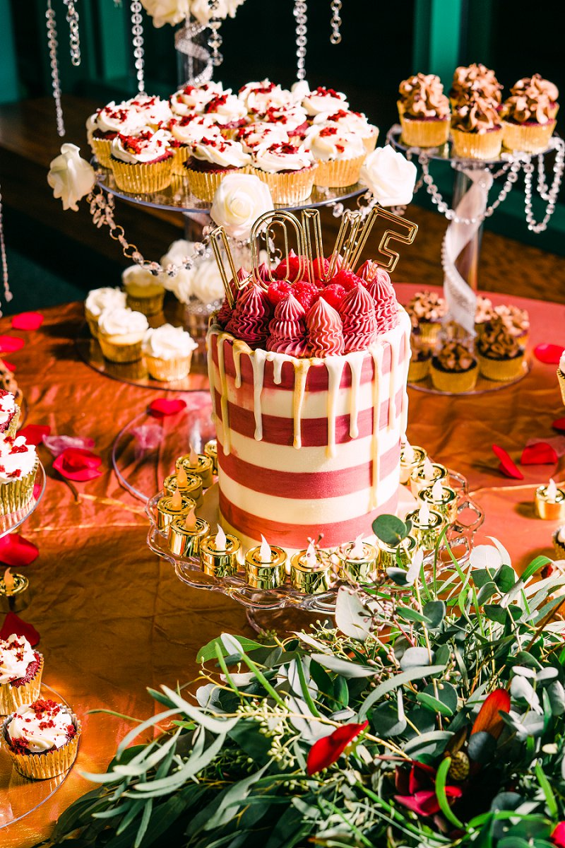 Red white and gold wedding cake and cupcake display for a chic intimate wedding desserts at the Virginia Living Museum in Newport News