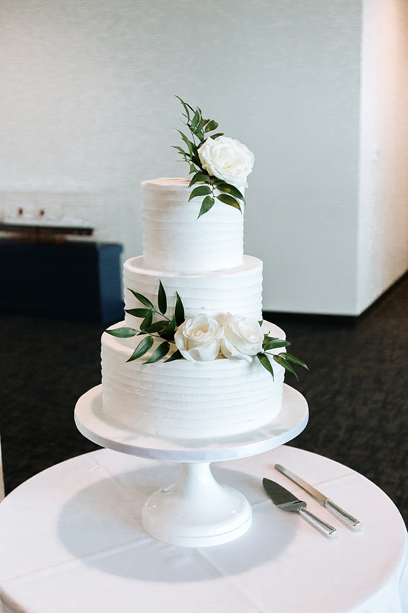Simply textured three tier white wedding cake with minimal white roses and florals for a chic modern wedding dessert