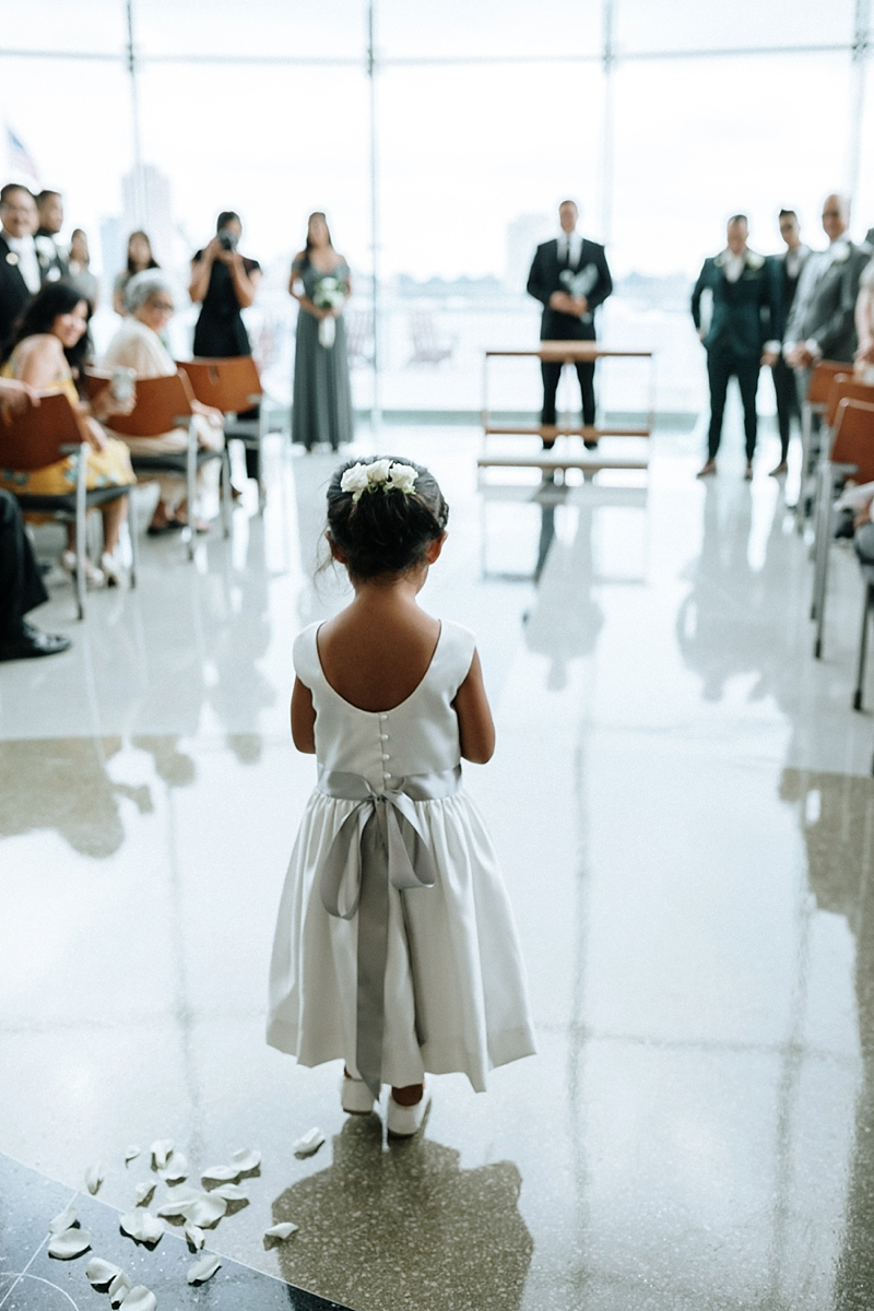 Adorable flower girl wearing a white and silver gray dress right before she goes down the aisle during the wedding ceremony in Norfolk Virginia